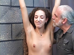 Beautiful young shaved pussy brunette is restrained in dungeon be incumbent on spanking