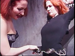 Curvy redhead shackled by lingere dominatrix