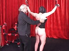 Spread-eagled shackled woman in leather mask added to enforcer gets caned on the brush ass