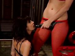 Blonde in red fishnet stockings and two brunettes play with strapon